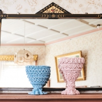 Pair of artworks, blue and pink cups, on shelf.