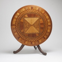 Table top folded down with circular top towards viewer showing inlay work.