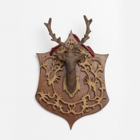 Stag's head mounted on crest-shaped backing.