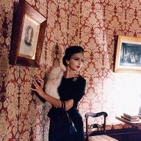 Woman in 1940s clothing next to a patterned wallpapered wall