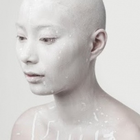 Woman with Asian heritage covered in white paint on white background