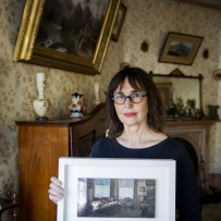 Woman seated in wallpapered room holding framed artwork.