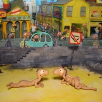 Two naked characters lie on a beach with a street scene in the background