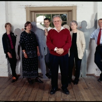 Group of people in white walled room with lifesize cutout figures behind.