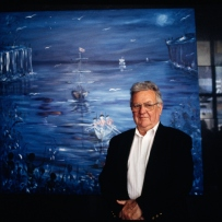 Man in front of large, mostly blue painting.