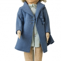 This is a photograph of a doll is a blue coat and hat