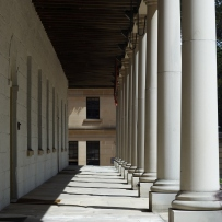verandah of the Mint building. Sandstone pillars on the right with the front wall on the left funnel off to show a sandstone wall at the end