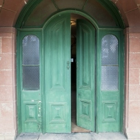 Arched doorway with green painted door partially open.