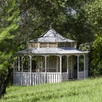 White circular building with verandah, framed by trees.