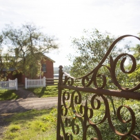 View through gateway towards pink schoolhouse building behind white fence.