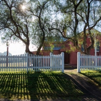 White picket fence in front of two trees and building.