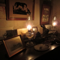 Kerosene lamps illuminating framed pictures and wallpaper behind.