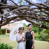 Two women, one dressed in white with white parasol, the other in black with black hat, under tree branches with man and house in background.