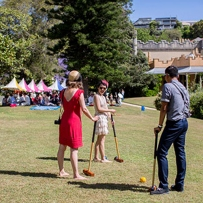 Three people playing croquet.