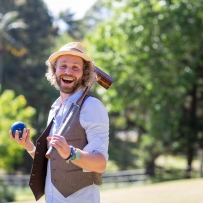 Bearded man looking at the camera. He is wearing a straw hat and is smiling. Trees can be seen in the background and it is a sunny day.