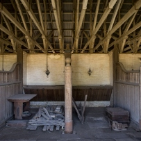 Looking into stalls, which are filled with lumber and other furniture.