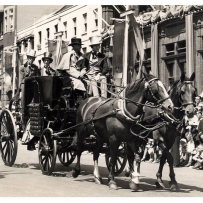Coach and horses in street parade.