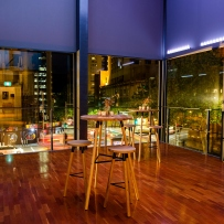 Glasswalled room looking out on cityscape at night.