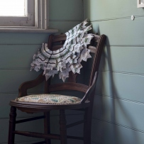 Intricately layered circular collar draped over wooden chair near sunlit window.