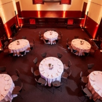 Room set for dinner with round tables.