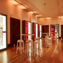 Gallery space with polished wooden floor set up for function.