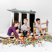 Kids build towers with LEGO in front of a model of Marina Bay Sands.
