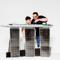 Ryan McNaught and boy look at LEGO model.