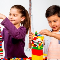 Two kids build towers from LEGO bricks.