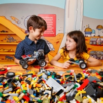 Exhibition view of a girl and a boy playing with Lego bricks