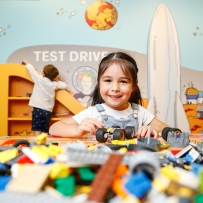 Exhibition view of a girl playing with Lego bricks