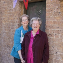 Two women outside doorway in brick wall with bunting overhead.