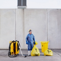 Man in blue uniform with yellow cleaning equipment and plastic bags.