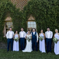Wedding photo outside arched windows.