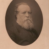 Oval black and white photograph of full bearded man.