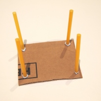 Cardboard table top with yellow straws blu-tacked on as legs.