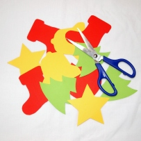 A selection of Christmas themed shapes in coloured paper with scissors.
