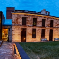 Panoramic view of sandstone building and courtyard at night with lighting on buildings.