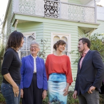 Three women and one man standing in front of green timber house.