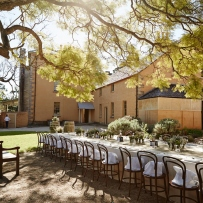 Long table setting outdoors under tree with house in background.