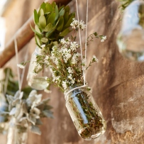 Jar hanging from wall with flowers.