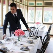 Man setting table with silverware and glassware.