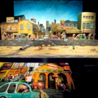 View of a diorama installed at in the exhibition. A graphic panel can be seen in the foreground with two naked characters on a beach behind.