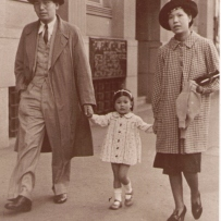 This is a black and white photograph of a Chinese couple walking down a Sydney street in Western clothes with a young female child walking between them and holding their hands