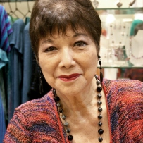 Photo of Vivian wearing patterned top and bead necklace.