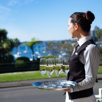 Woman in waiting outfit holding tray of drinks with view of harbour in background