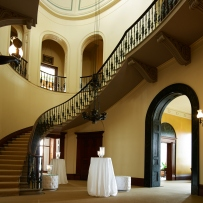 Foyer and staircase with tables set up for event.
