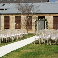 Seating on lawn with white runner leading up to floral arch and sandstone building behind.