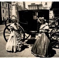 Two women in period costume in front of coach.
