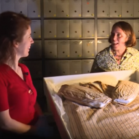 Two women talking while examining shirt in collection items box.