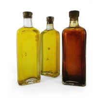 Three glass bottles with oil, two yellow, one darker brown in colour.